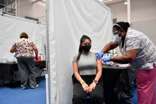 A nurse administers a dose of the Moderna Covid-19 vaccine at a clinic at a vaccination site at Loyola Marymount University on March 8, 2021.
