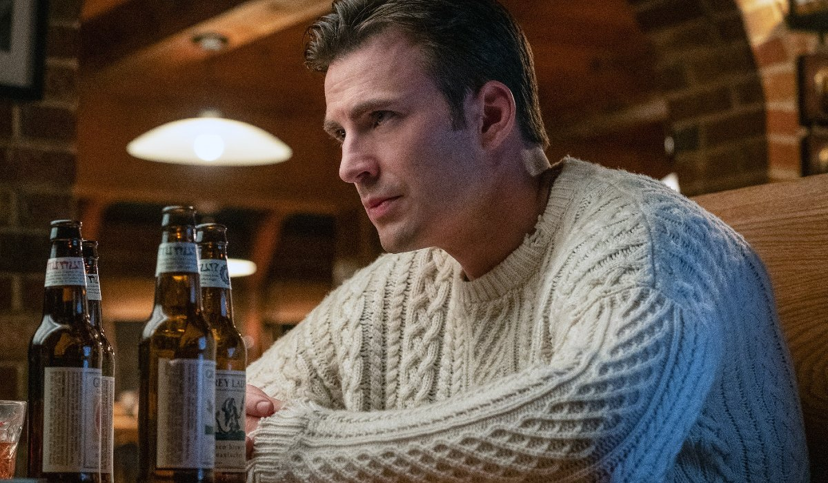 """Chris Evans wears """"the sweater"""" with a couple of beers on the table in Knives Out."""