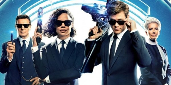 Men In Black International full cast lined up with poses in front of a glowing portal