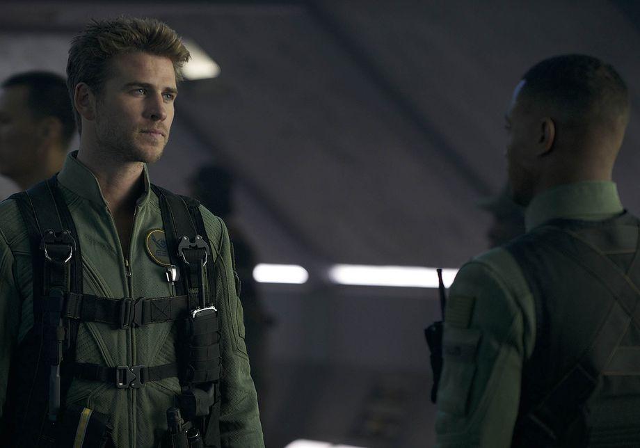 Liam Hemsworth in a flight suit talks to a colleague