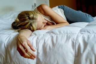 Depressed woman lying in bed.