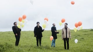 A press shot of Cold Reading looking happy with balloons