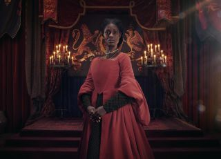 Jodie Turner-Smith as Anne Boleyn, wearing a red dress and standing in the throne room