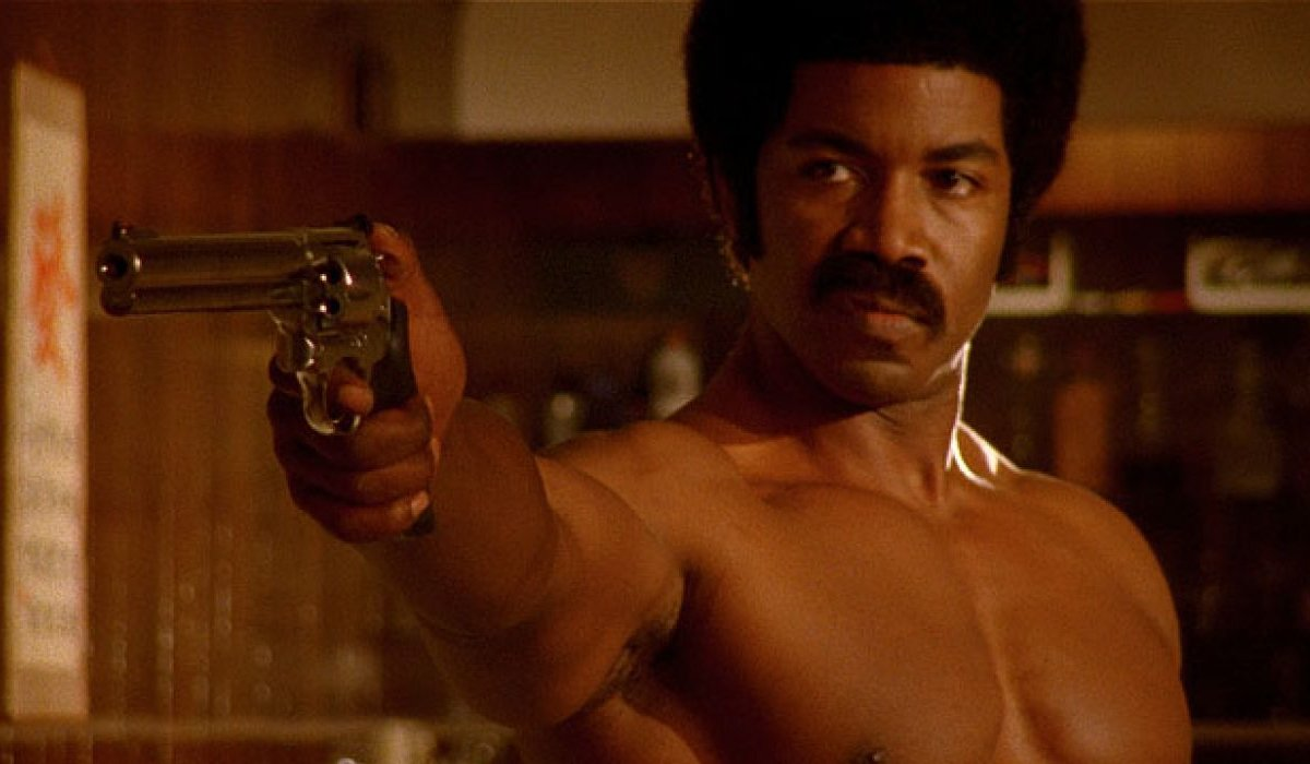 Black Dynamite Michael Jai White stands shirtless, with a gun