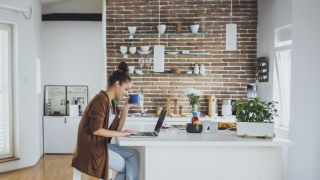 Brick Slips Woman in kitchen with exposed brick wall