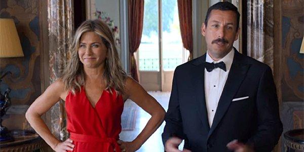 Netflix Murder Mystery Jennifer Aniston red dress hands on hips Adam Sander tuxedo