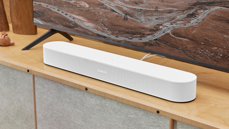 Sonos Beam 2 in white finish on wooden TV bench, with TV positioned behind it