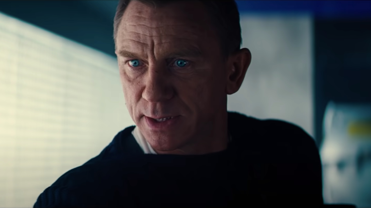 No Time To Die Daniel Craig looks concerned while standing in a lab