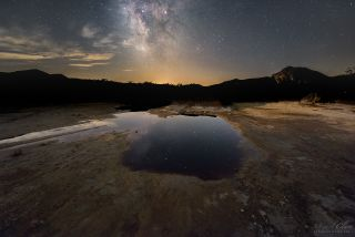 Milky Way reflected in acid water puddle