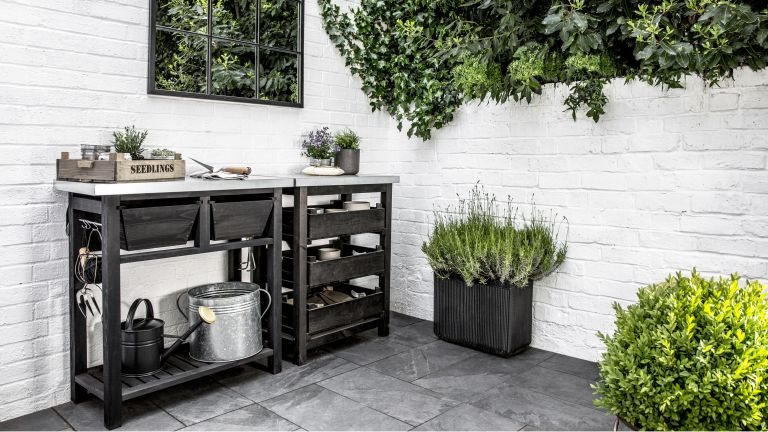 Potting bench on a courtyard patio with a garden mirror on one wall