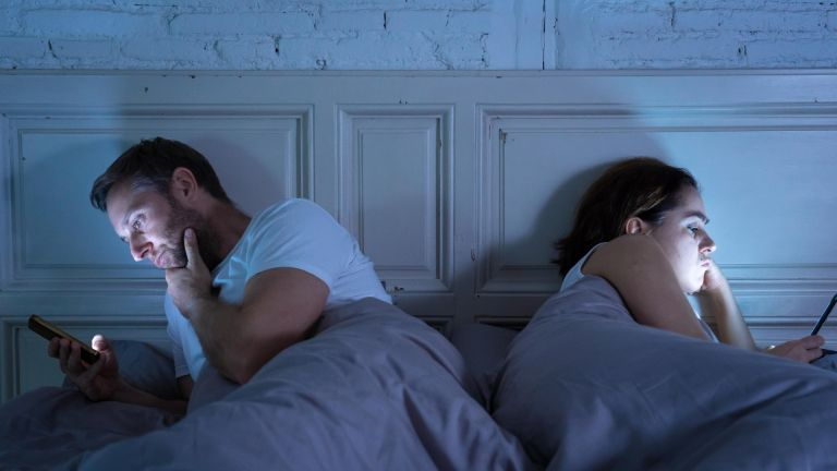 Young couple in bed late at night using smart phones obsessed with games, social media and apps ignoring each other in relationship communication prob