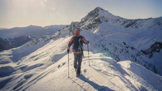 A climber crossing a snowy peak