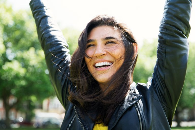woman smiles with her hands in the air