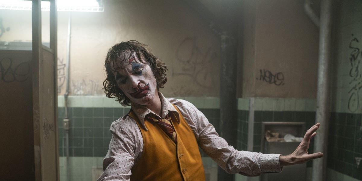 The Joker (Joaquin Phoenix) dances in a grimy bathroom.