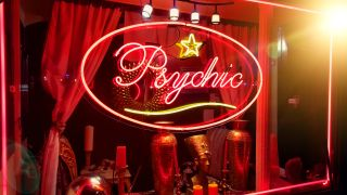 """Neon """"psychic"""" sign in a shop window."""