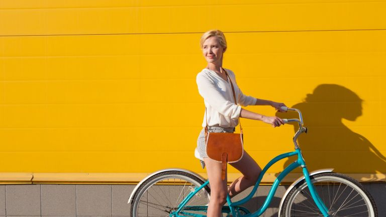 Woman on a bike cycling against a yellow wall