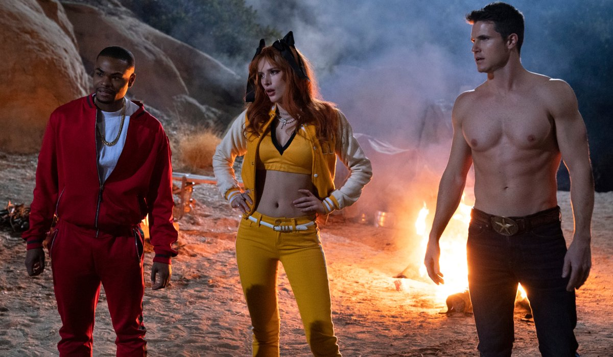 The Babysitter: Killer Queen Andrew Bachelor, Bella Thorne, and Robbie Amell with their backs turned to a roaring fire