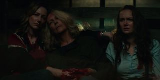 Karen holds a bleeding Laurie while they sit next to Allyson in 2018's Halloween