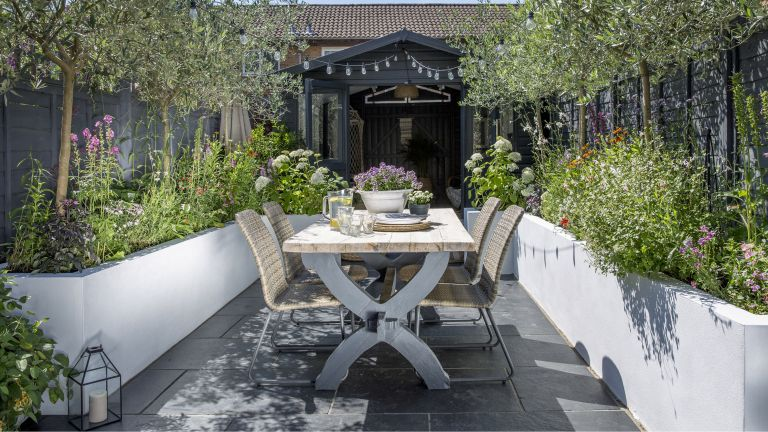 Patio gardening ideas: patio surrounded by raised beds with a shed at the far end and festoon lights
