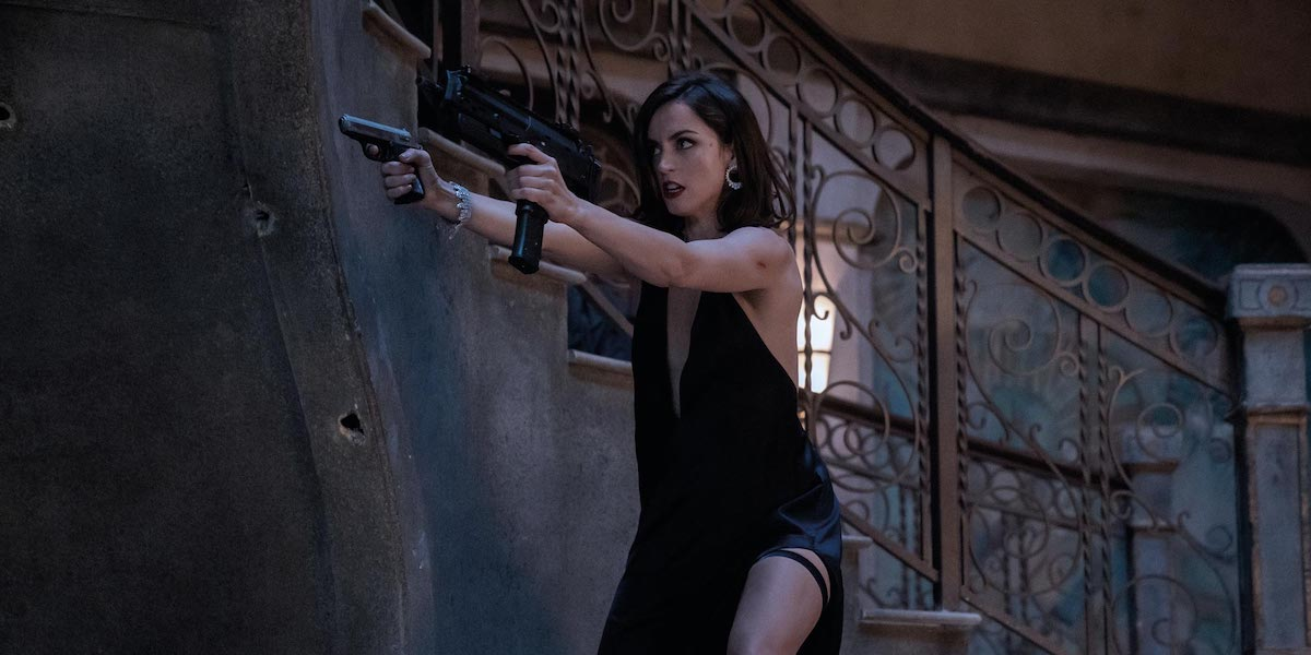 Paloma (Ana de Armas) points her guns at an unseen foe in 'No Time to Die'
