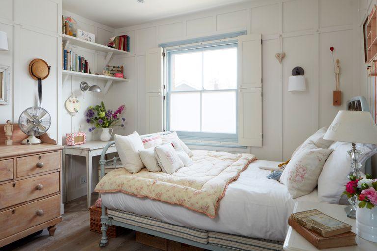 bedroom with pastel bedlinen and bookshelf