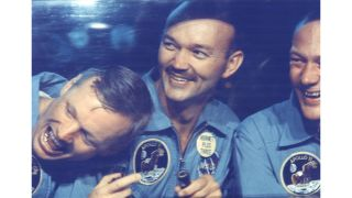 The Apollo 11 crew smiles in quarantine after their mission. From left, astronauts Neil Armstrong, Michael Collins and Buzz Aldrin.
