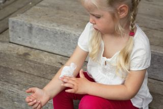 A little girl spreads lotion over her arm