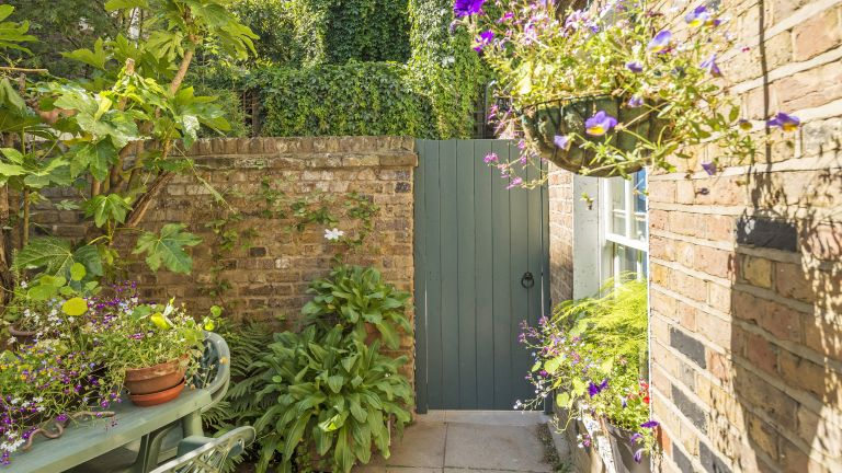 garden gate ideas showing a painted wooden garden gate in a stone wall