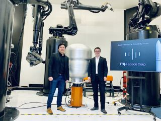 Mu Space CEO & Founder James Yenbamroong (left) and Relativity Space CEO & Founder Tim Ellis (right) stand in front of Relativity's Stargate, the world's largest metal 3D printer.