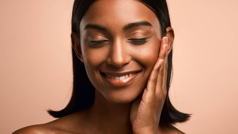 Shot of a beautiful young woman touching her face while posing against a brown background