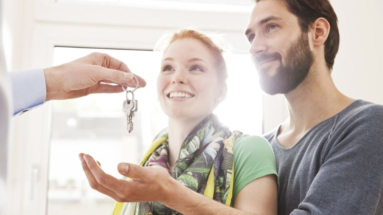 young couple being handed the keys to their new home