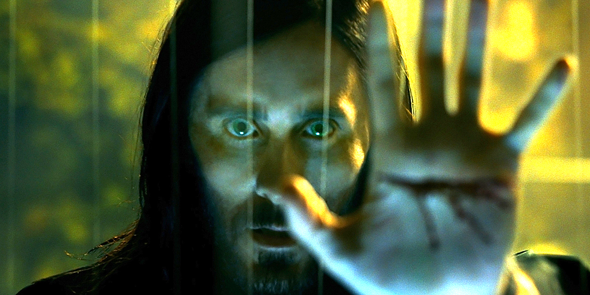 Morbius (Jared Leto) puts his bleeding hand on a glass wall and stares into the camera.
