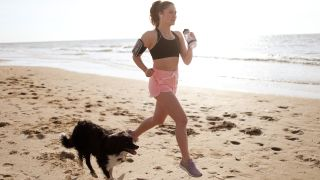 A woman jogging on the beach alongside one of the best dogs for runners