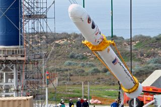 At Vandenberg Air Force Base in California, Orbital Sciences workers monitor NASA's Glory upper stack as a crane lifts the Earth-observation satellite from a stationary rail for attachment to the Taurus XL rocket's Stage 0. Glory launched in March 2011 but failed to reach orbit.