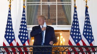 U.S. President Donald Trump removes his mask upon return to the White House from Walter Reed National Military Medical Center on Oct. 05, 2020, in Washington, D.C.