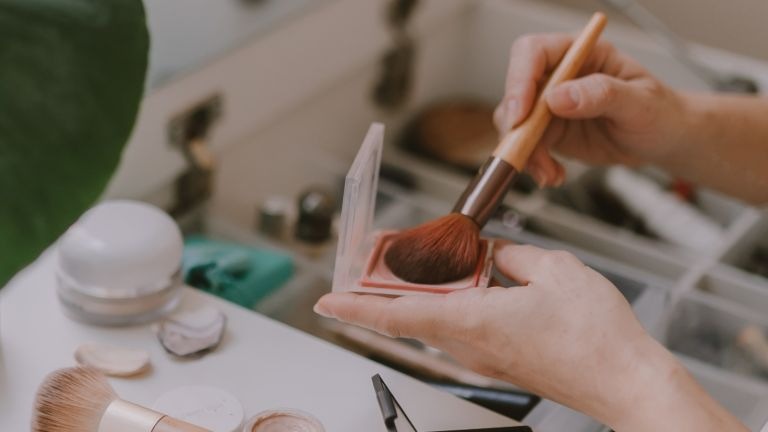 Cropped Hand Of Woman Holding Make Up Brush - stock photo