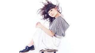 Hiromi sitting on a chair with a striped top