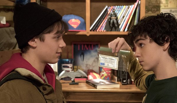Angel Asher as Billy Batson looking at superhero stuff in Shazam