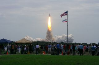 atlantis flies with spectators watching the launch