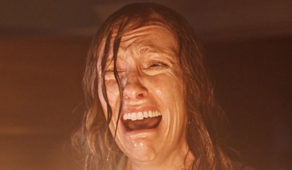 Hereditary Toni Collette looks frightened in front of a blazing fire