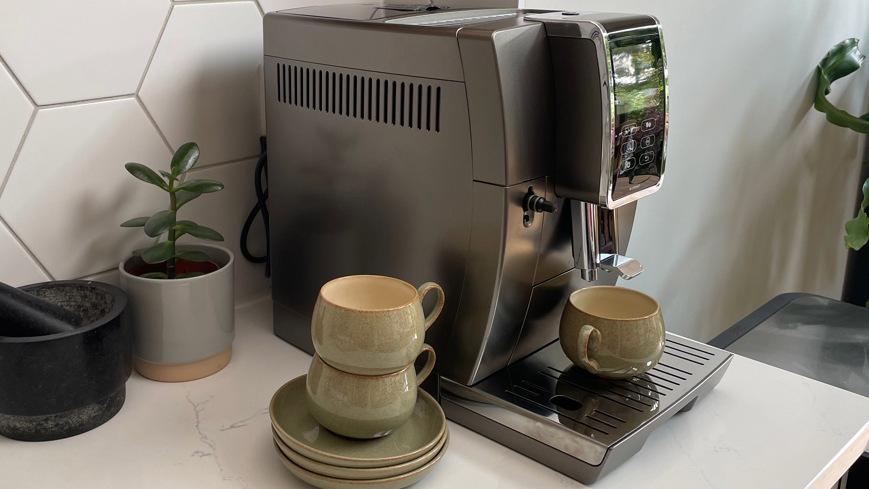 The side of the De'Longhi Dinamica Plus coffee maker on a kitchen countertop with a cup ready to pour an espresso