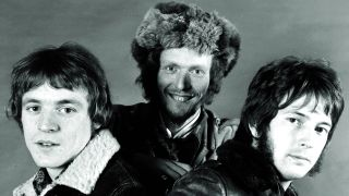 Jack Bruce, Ginger Baker and Eric Clapton of Cream, looking at the camera.