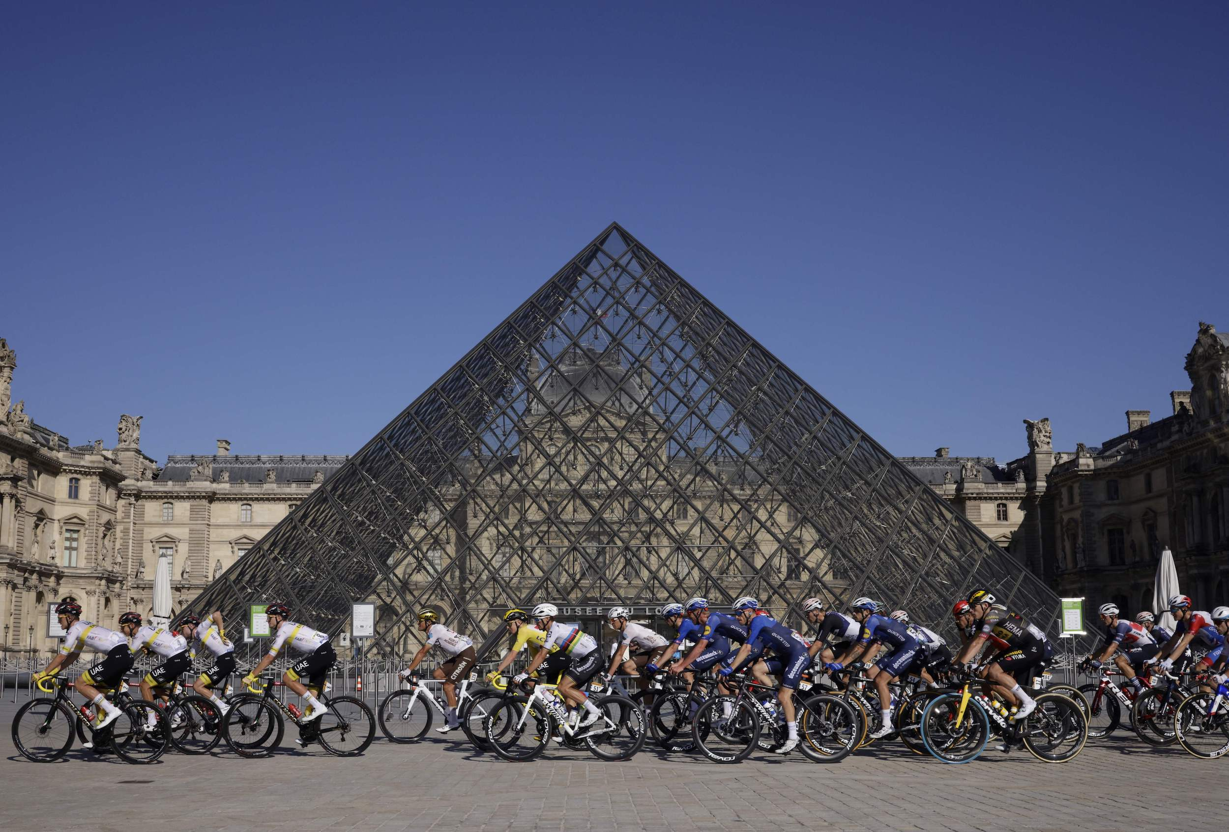 Peloton rides in front of the pyramid at the Louvre