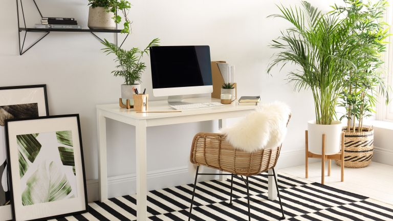 Rattan chair under white desk with computer on