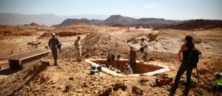"Archaeologists excavate a copper production site dubbed ""Slaves' Hill"" in the Timna Valley, Israel, with mountains in the background"