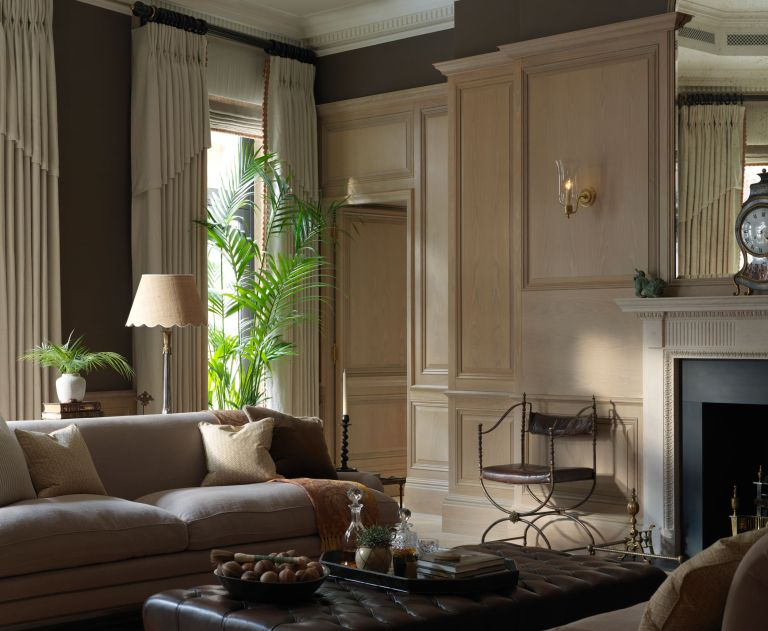 classic living room with panelling and trad features, neutral scheme with wall light and table lamp, full drapes