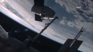 A robotic arm at the International Space Station captures an unmanned Dragon space capsule as it delivered supplies, including a DNA sequencer, to the outpost's crew on July 20, 2016.