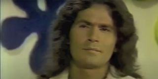 Rodney Alcala with long hair sitting on a chair playing The Dating Game.