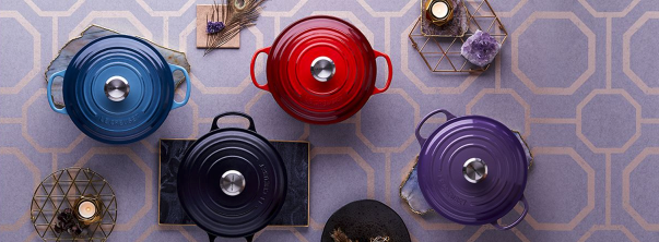 Le Creuset pots on a purple background