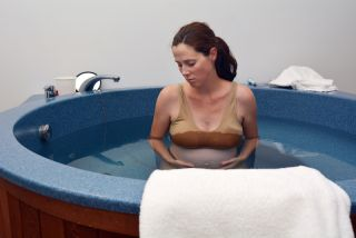 A pregnant woman sits in a tub filled with water.